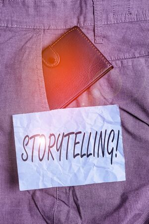 Text sign showing Storytelling. Business photo showcasing activity writing stories for publishing them to public Small little wallet inside man trousers front pocket near notation paper Stok Fotoğraf