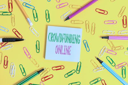 Handwriting text writing Crowdfunding Online. Conceptual photo raising small amounts of money from analysisy showing Flat lay above empty paper with copy space pencils and colored paper clips