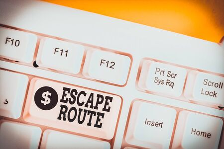 Text sign showing Escape Route. Business photo showcasing a route by which a demonstrating may reach a place of safety White pc keyboard with empty note paper above white background key copy space 写真素材