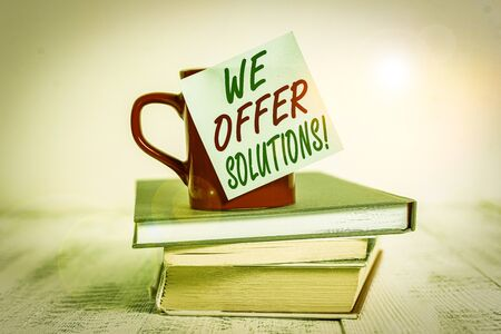 Conceptual hand writing showing We Offer Solutions. Concept meaning way to solve problem or deal with difficult situation Coffee cup sticky note stacked books retro old retro wooden table Zdjęcie Seryjne