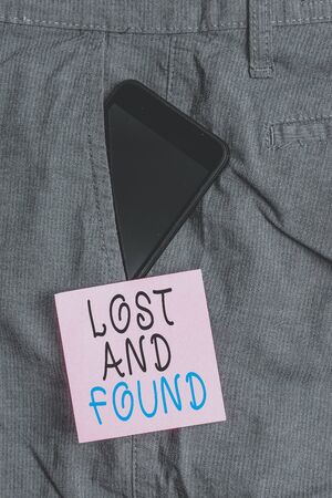Handwriting text Lost And Found. Conceptual photo Place where you can find forgotten things Search service Smartphone device inside formal work trousers front pocket near note paper