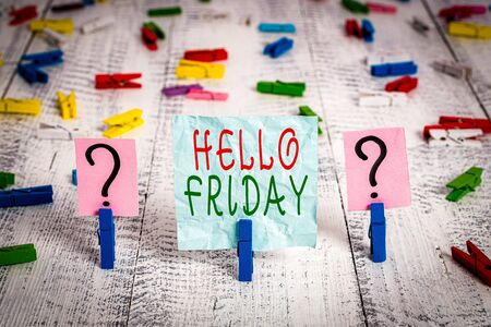 Conceptual hand writing showing Hello Friday. Concept meaning Greetings on Fridays because it is the end of the work week Crumbling sheet with paper clips placed on the wooden table