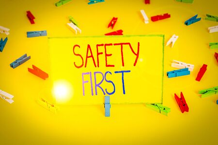 Word writing text Safety First. Business photo showcasing used to say that the most important thing is to be safe Colored clothespin papers empty reminder yellow floor background office
