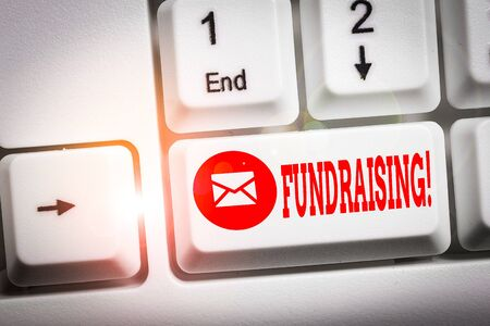 Conceptual hand writing showing Fundraising. Concept meaning seeking to generate financial support for charity or cause Keyboard with note paper on white background key copy space