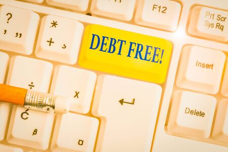 Writing note showing Debt Free. Business concept for does not owning any money to any individual or companies White pc keyboard with note paper above the white background