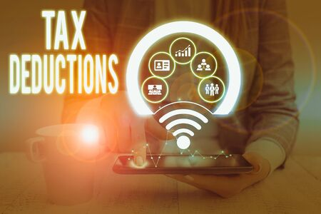 Writing note showing Tax Deductions. Business concept for reduction income that is able to be taxed of expenses Picture photo network scheme with modern smart device 写真素材