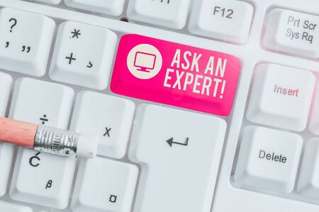 Conceptual hand writing showing Ask An Expert. Concept meaning confirmation that have read understand and agree with guidelines White pc keyboard with note paper above the white background Zdjęcie Seryjne