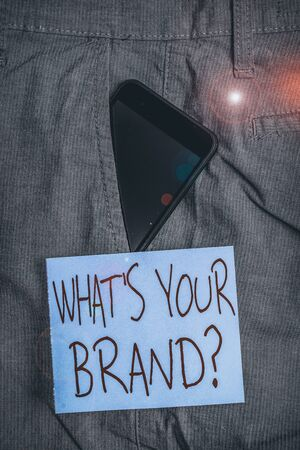Word writing text Whats  Your Brand Question. Business photo showcasing asking about product logo does or what you communicate Smartphone device inside formal work trousers front pocket near note paper