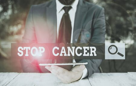 Word writing text Stop Cancer. Business photo showcasing prevent the uncontrolled growth of abnormal cells in the body Businessman with mobile phone in his hand
