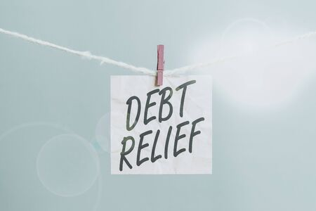 Text sign showing Debt Relief. Business photo showcasing a reduction in the amount of debt that a country has to pay Clothesline clothespin rectangle shaped paper reminder white wood desk Zdjęcie Seryjne