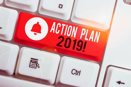 Text sign showing Action Plan 2019. Business photo showcasing proposed strategy or course of actions for current year White pc keyboard with empty note paper above white background key copy space