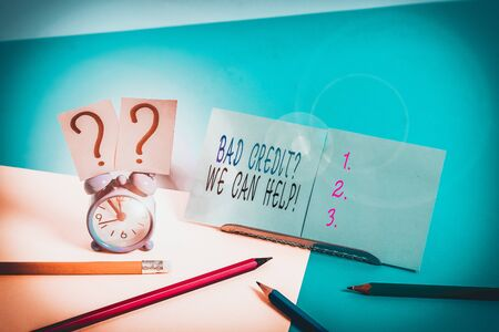 Writing note showing Bad Creditquestion We Can Help. Business concept for offerr help to gain positive payment history Mini size alarm clock beside stationary on pastel backdrop
