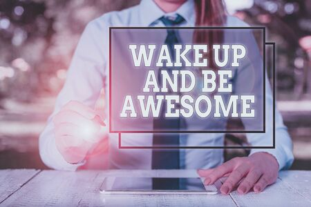 Text sign showing Wake Up And Be Awesome. Business photo showcasing Rise up and Shine Start the day Right and Bright Female business person sitting by table and holding mobile phone
