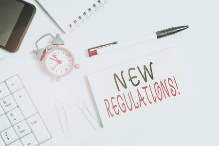 Text sign showing New Regulations. Business photo text rules made government order control something done Flat lay above computer mobile phone clock pencil and copy space note paper