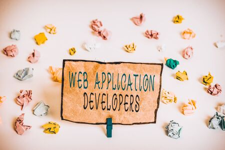 Text sign showing Web Application Developers. Business photo text Internet programming experts Technology software Colored crumpled papers empty reminder white floor background clothespin