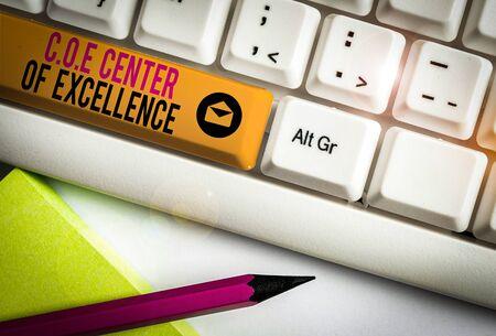 Handschriftlicher Text Coe Center of Excellence. Konzeptionelles Foto als Alpha-Leader in Ihrer Position Erzielen Sie eine weiße PC-Tastatur mit leerem Notizpapier über dem weißen Hintergrund-Tastenkopierraum Standard-Bild
