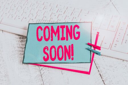 Handwriting text Coming Soon. Conceptual photo event or action that will happen after really short time notebook paper reminder clothespin pinned sheet white keyboard light wooden