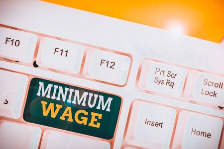 Word writing text Minimum Wage. Business photo showcasing the lowest wage permitted by law or by a special agreement White pc keyboard with empty note paper above white background key copy space