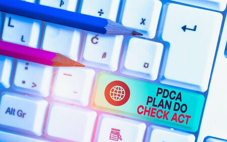 Writing note showing Pdca Plan Do Check Act. Business concept for Deming Wheel improved Process in Resolving Problems White pc keyboard with note paper above the white background