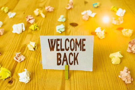Writing note showing Welcome Back. Business concept for something back to greet the return of someone or something Colored crumpled papers wooden floor background clothespin