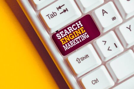 Writing note showing Search Engine Marketing. Business concept for promote Website visibility on searched result pages White pc keyboard with note paper above the white background Foto de archivo