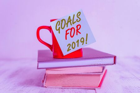 Conceptual hand writing showing Goals For 2019. Concept meaning object of demonstratings ambition or effort aim or desired result Coffee cup sticky note stacked books retro old retro wooden table