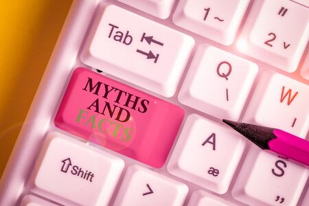Conceptual hand writing showing Myths And Facts. Concept meaning Oppositive concept about modern and ancient period White pc keyboard with note paper above the white background
