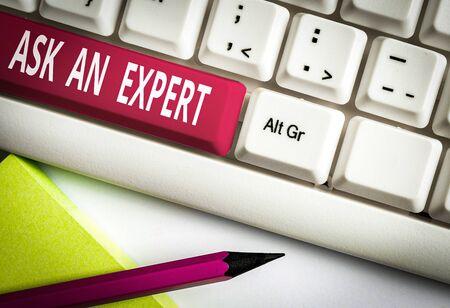 Tekstbord met vraag het aan een expert. Zakelijke fototekst raadpleeg iemand die ergens over beschikt of goed geïnformeerd is Wit pc-toetsenbord met leeg notitiepapier boven witte achtergrondsleutelkopieruimte