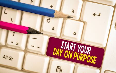 Conceptual hand writing showing Start Your Day On Purpose. Concept meaning Have clean ideas of what you are going to do White pc keyboard with note paper above the white background