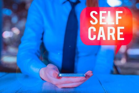 Writing note showing Self Care. Business concept for the practice of taking action to improve one s is own health Female business person sitting by table and holding mobile phone