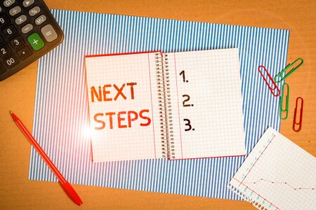 Text sign showing Next Steps. Business photo text something you do or plan after you ve finished something else Striped paperboard notebook cardboard office study supplies chart paper