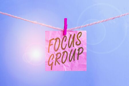 Text sign showing Focus Group. Business photo showcasing showing assembled to participate in discussion about something Clothesline clothespin rectangle shaped paper reminder white wood desk 版權商用圖片