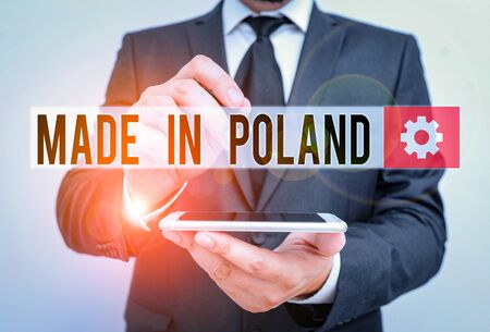 Text sign showing Made In Poland. Business photo text A product or something that is analysisufactured in Poland Male human wear formal work suit hold smart hi tech smartphone use one hand