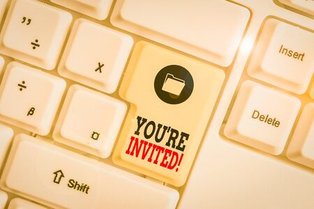 Text sign showing You Re Invited. Business photo showcasing make a polite friendly request to someone go somewhere White pc keyboard with empty note paper above white background key copy space