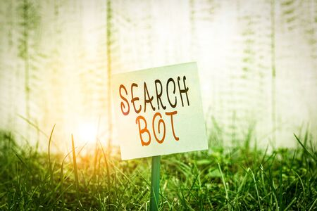 Text sign showing Search Bot. Business photo showcasing a program that runs automated tasks over the Internet or network Plain empty paper attached to a stick and placed in the green grassy land