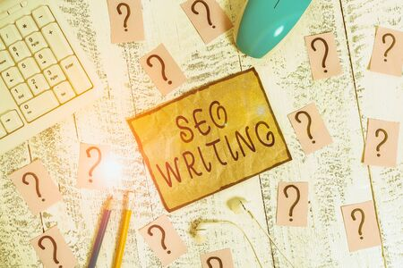 Conceptual hand writing showing Seo Writing. Concept meaning grabbing the attention of the search engines using specific word Writing tools and scribbled paper on top of the wooden table
