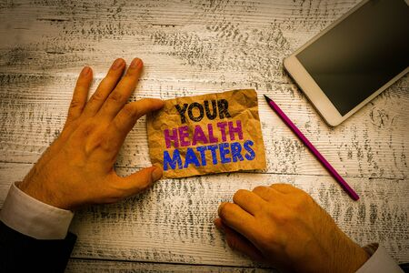 Handwriting text Your Health Matters. Conceptual photo good health is most important among other things Hand hold note paper near writing equipment and modern smartphone device Reklamní fotografie - 137798819