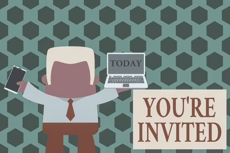 Word writing text You Re Invited. Business photo showcasing Please join us in our celebration Welcome Be a guest Standing professional man tie holding left open laptop right mobile phone Reklamní fotografie