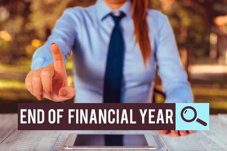 Handwriting text writing End Of Financial Year. Conceptual photo Revise and edit accounting sheets from previous year Female business person sitting by table and holding mobile phone