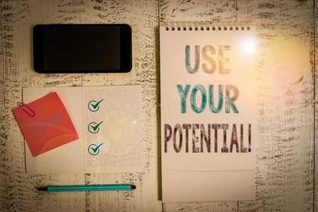 Writing note showing Use Your Potential. Business concept for achieve as much natural ability makes possible Square spiral notebook marker smartphone sticky note on wood background Фото со стока