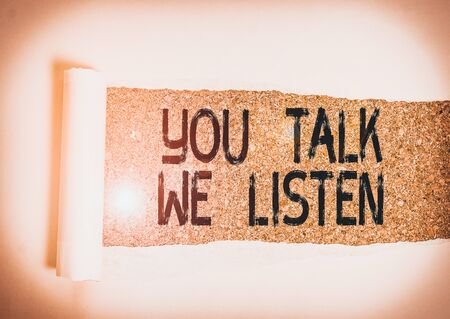 Conceptual hand writing showing You Talk We Listen. Concept meaning Two Way Communication Motivational Conversation Cardboard which is torn placed above a wooden classic table
