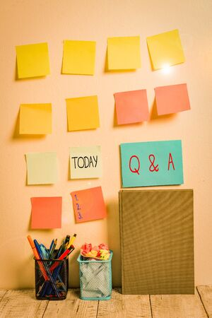 Conceptual hand writing showing Q And A Question. Concept meaning in which demonstrating asks questions and another one answers them Sticky Notes Card on Wall Pencil Pots Notebook on Work Desk