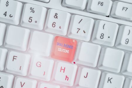 Text sign showing Small Business Solutions. Business photo showcasing a Company to solve Specific Trade problems White pc keyboard with empty note paper above white background key copy space