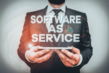 Text sign showing Software As Service. Business photo text On Deanalysisd licensed on Subscription and centrally hosted Male human wear formal work suit hold smart hi tech smartphone use hands
