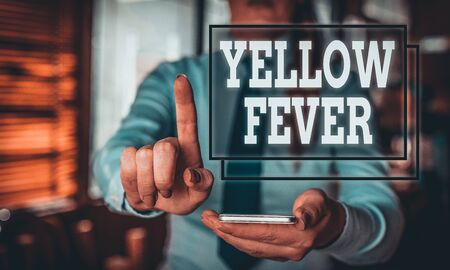 Conceptual hand writing showing Yellow Fever. Concept meaning tropical virus disease affecting the liver and kidneys Woman in the background pointing with finger in empty space