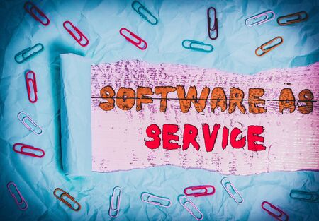 Writing note showing Software As Service. Business concept for On Deanalysisd licensed on Subscription and centrally hosted Paper clip and torn cardboard on wood classic table backdrop Stock Photo