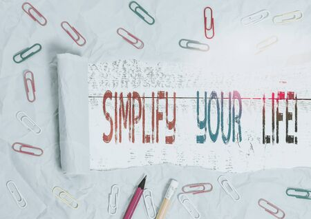 Word writing text Simplify Your Life. Business photo showcasing focused on important and let someone else worry about less ones Stationary and torn cardboard placed above a wooden classic table backdrop