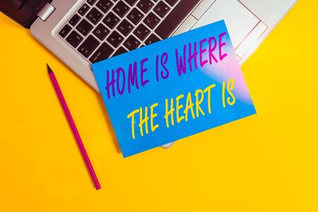 Conceptual hand writing showing Home Is Where The Heart Is. Concept meaning Your house is where you feel comfortable and happy Metallic laptop small paper sheet pencil colored background