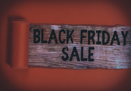 Word writing text Black Friday Sale. Business photo showcasing Shopping Day Start of the Christmas Shopping Season Cardboard which is torn in the middle placed above a wooden classic table