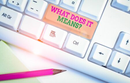 Text sign showing What Does It Means Question. Business photo showcasing asking meaning something said and do not understand White pc keyboard with empty note paper above white background key copy space